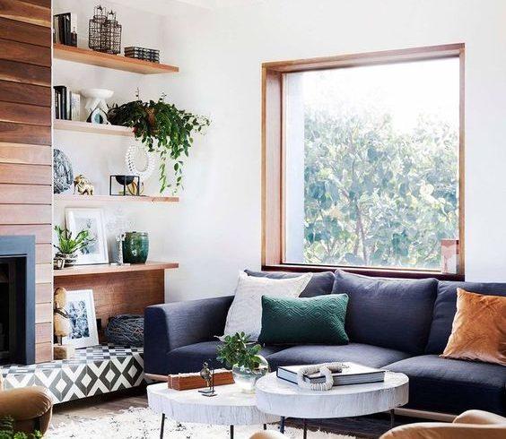 salon z drewnianymi elementami i ciemną sofą